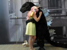 Godzilla Cosplayer Hugging Anime Flower Girl Cosplayer